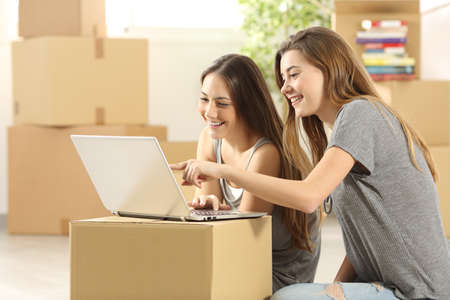 Happy roommates searching on line with a laptop on a cardboard box and moving home sitting on the floor of the living room Banco de Imagens