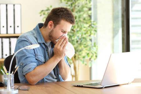 Vista laterale di un imprenditore malato starnutire in un wipe presso l'ufficio vicino ad una finestra Archivio Fotografico - 71171581