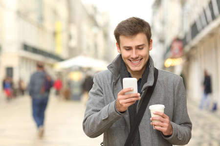 man coffee: Front view portrait of a businessman walking towards camera and using a smart phone in the street in winter Stock Photo