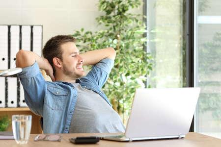 リラックスして、デスクトップで座っていると、事務所の窓を通して見るを考えて起業家の側面図