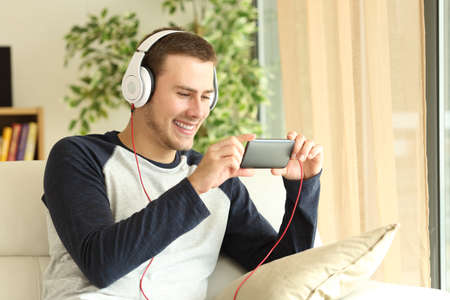 Handsome guy listening and watching media content on line in a smartphone sitting on a sofa in the living room at home