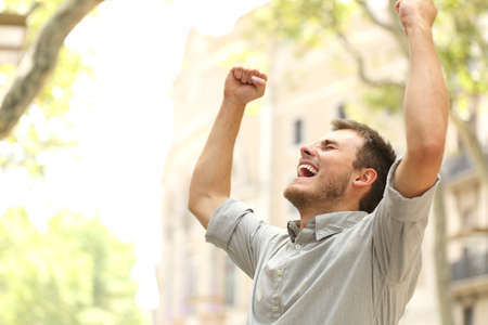 Portrait of an excited man raising arms in the street with buildings in the background Stockfoto