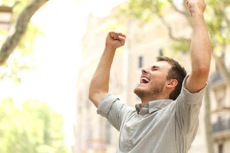 Ritratto di un uomo eccitato che alza le braccia in strada con gli edifici in background