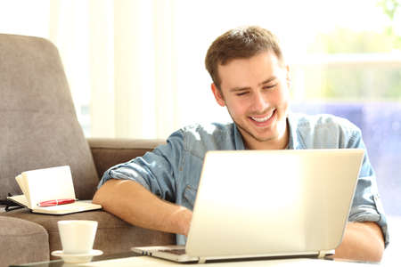 develope: Front view of a man working with a laptop sitting on the floor of the living room at home Stock Photo