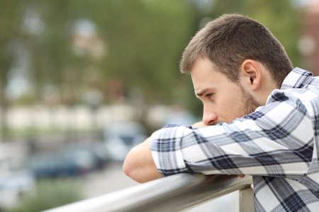도시 배경 가진 집의 발코니에서 내려다보고 슬픈 단일 남자의 측면보기 초상화