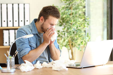 Portrait of a sick entrepreneur blowing in a wipe at office with a lot of used wipes on the desk Stockfoto