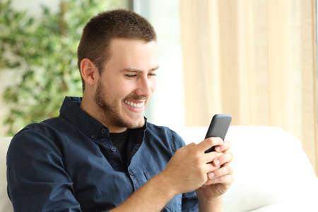downloading content: Portrait of a happy casual guy using a mobile phone sitting on a sofa in the living room at home with a window in the background