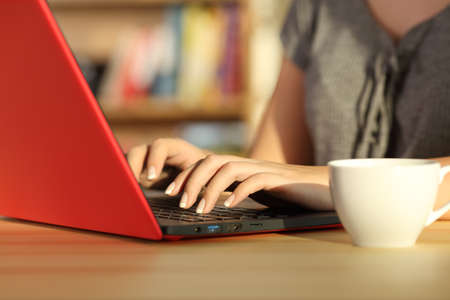 Close up of girl hands writing in a red laptop on a table at home with a warm light and a colorful background