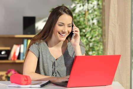 Happy student asking information by phone consulting a laptop on line sitting in a table at home with a colorful background