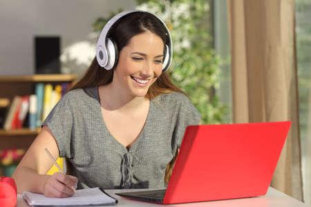 Hermoso retrato de un estudiante que aprende en línea viendo tutoriales en vídeo con un ordenador portátil y los auriculares de color rojo en una mesa en su casa