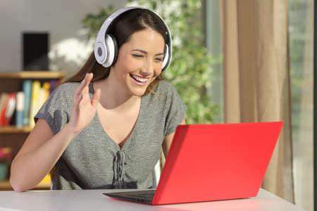 リビング ルームのテーブルに座っている赤いノート パソコン ラインのビデオ会議中に挨拶のヘッドフォンを身に着けている幸せな女 写真素材