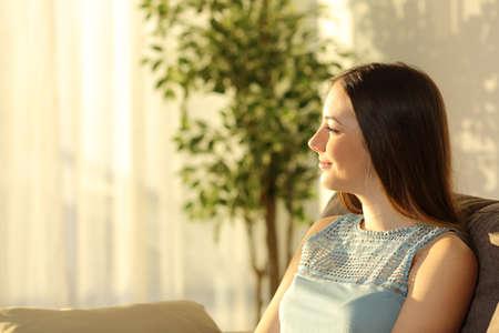 집 창문 및 백그라운드에서 따뜻한 빛을 가진 집 인테리어에 거실에 소파에 앉아 일몰을 생각 하 고 한 여자의 측면보기