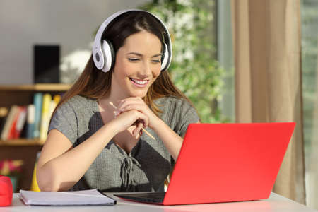 Portrait of a beautiful student viewing and listening video tutorials on line with headphones and a red pc sitting in a table at home 版權商用圖片 - 71232726