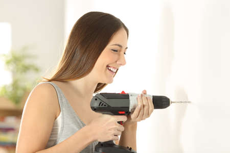 Happy girl using a battery drill in a wall in the living room at home