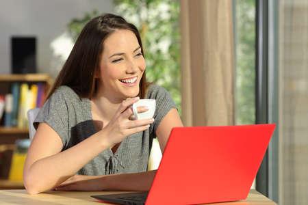 リラックスして、自宅の窓から見て考えてコーヒーのカップを保持しているラップトップで幸せな女