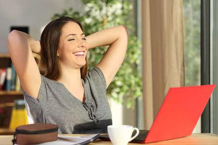 Spokojený student odpočívá s rukama na hlavě sedí na židli a dívá se přes okno v obývacím pokoji doma Reklamní fotografie
