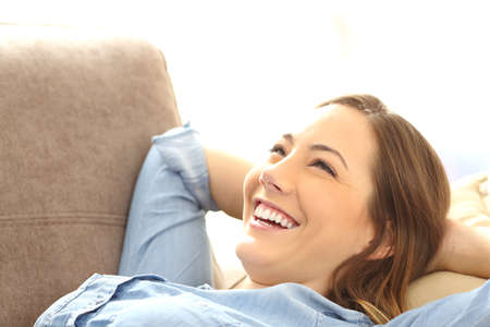 householder: Portrait of a single happy woman relaxing and laughing after work lying on a sofa in the living room at home Stock Photo