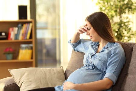 自宅の居間でソファに座って心配して妊娠中の女性