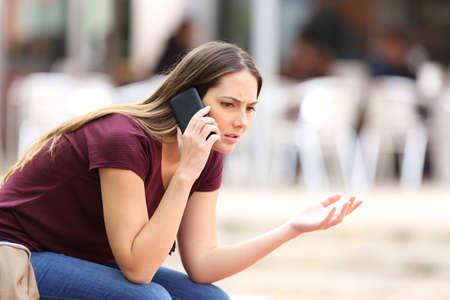 Enojado mujer casual llamando al teléfono sentado en un banco en la calle Foto de archivo