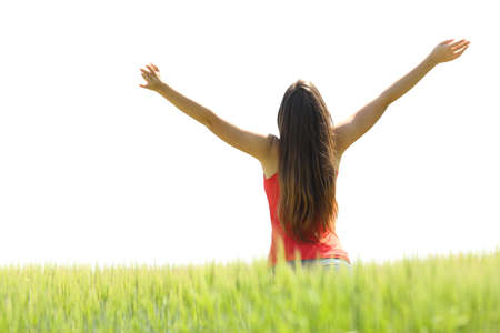 Back view of a happy woman raising arms in a field with a white sky in the background