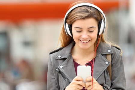 music lyrics: Vista frontal de una música que escucha de la muchacha de la manera con los auriculares y el teléfono inteligente en línea y caminando hacia la cámara en la calle Foto de archivo