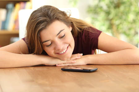 Happy teenager loving her smart phone and looking it waiting for a message at home