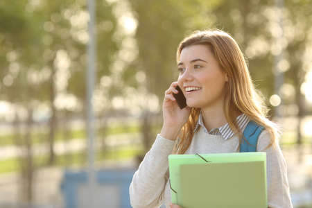 Happy student girl walking and calling on mobile phone  outdoors with a green background Stock Photo