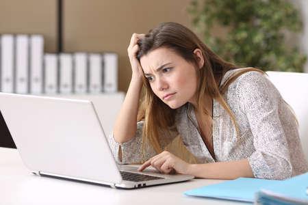 Tirocinante Confuso lavorare on line con un computer portatile in un compito difficile in ufficio Archivio Fotografico - 71234213