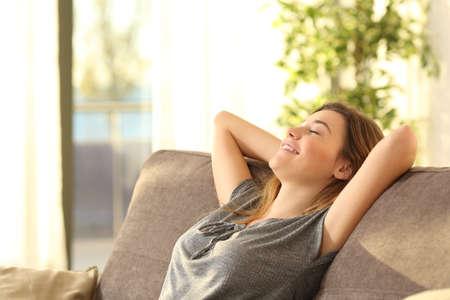 cansancio: Retrato de una chica de relax en un sofá después del trabajo en casa sentado en un sofá en la sala de estar en casa con una luz cálida del atardecer Foto de archivo