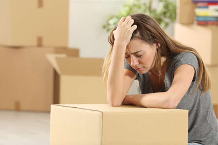 Sad homeowner moving home after eviction sitting on the floor of the living room at home