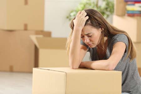 悲しいの自家所有者が自宅の居間の床に座って立ち退き後ホームに移動