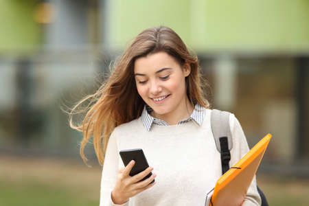 Single student walking and reading mobile phone messages with a university building in the background
