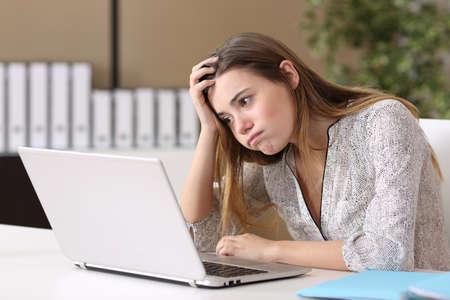 Pasante frustrado que intenta trabajar en línea con una computadora portátil en una tarea difícil en un escritorio con antecedentes de oficina