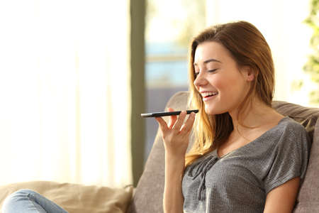 Chica usando un teléfono inteligente de reconocimiento de voz en la línea que se sienta en un sofá en la sala de estar en casa con una luz cálida y una ventana en el fondo