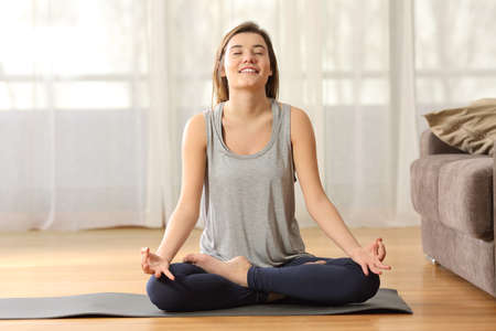 Front view full body portrait of a relaxed candid girl practicing yoga sitting on the floor in the living room at home