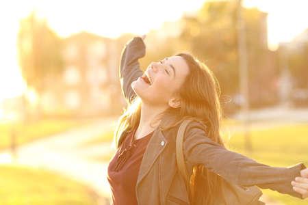 팔을 제기하고 백그라운드에서 따뜻한 빛으로 석양 거리에서 웃고 흥분된 십대 소녀의 세로
