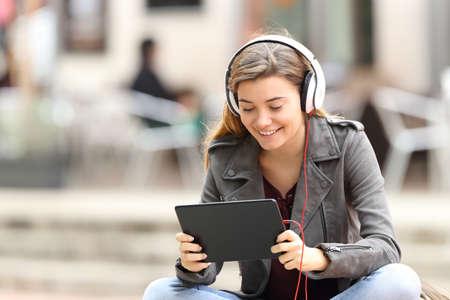아름 다운 패션 소녀 태블릿와 거리에서 벤치에 앉아 헤드폰 줄 학습