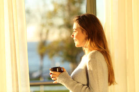 Side view portrait of a single relaxed girl looking the sea outside through a window and holding a coffee mug at sunset in the living room at home