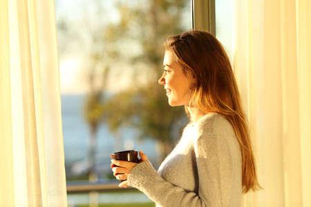 mujer mirando el horizonte: Vista lateral retrato de una chica sola relajado mirando el mar exterior a través de una ventana y la celebración de una taza de café al atardecer en el salón de su casa Foto de archivo