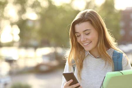 Un estudiante feliz caminando y usando el teléfono inteligente en línea en la calle al atardecer con una luz de fondo cálida Foto de archivo