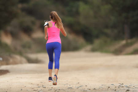 Back view of a runner wearing colorful sportswear running in the country Stock Photo