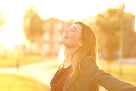 Zurück Licht Portrait eines glücklichen Single jugendlich Mädchen atmen frische Luft bei Sonnenuntergang in einem Park mit einem warmen gelben Licht und städtischen Hintergrund