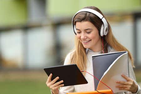 investigando: Único estudiante buscando información en línea con una tableta y comparando con un cuaderno en la calle sentado frente al edificio de la universidad Foto de archivo