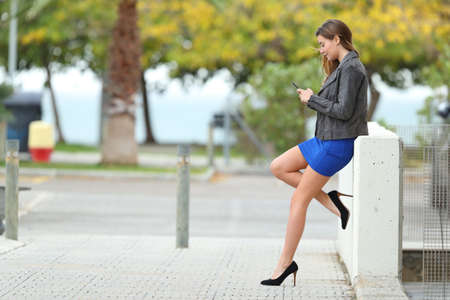 Zijaanzicht van een volledig lichaam van een maniermeisje met lange perfecte benen die telefoon in de straat met behulp van