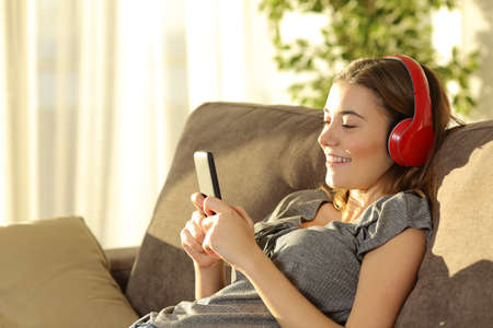 Single teen listening music on line with a smart phone and headphones sitting on a sofa n the living room at home