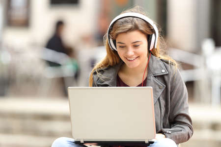 Casual girl listening music with headphones and searching songs in a laptop sitting on a bench in the street Stock Photo - 71234206