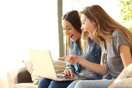 Twee opgewonden huisgenoten lezen van goed nieuws op lijn met een laptop zittend op een bank in de woonkamer thuis met een raam op de achtergrond