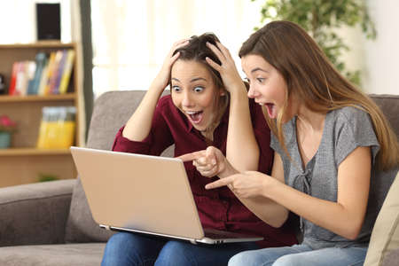 Two astonished roommates watching media content on line with a laptop sitting on a couch in the living room in a house interior