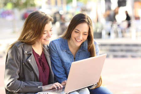 Two friends watching media content on line together with a laptop sitting in a bench in the street with an urban background