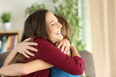 Two affectionate friends or sisters embracing with love in the living room at home Stock fotó